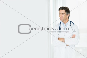 Thoughtful mature male doctor with arms folded