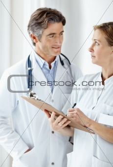 Doctor and nurse having a word on a patience's report