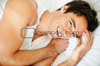 Portrait of a cheerful young guy waking up in morning on the bed