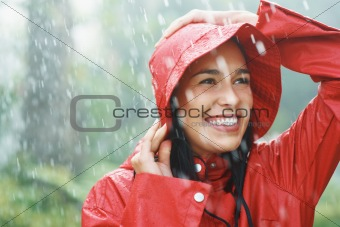 Woman smiling while holding rain coat