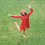 Woman in raincoat dancing