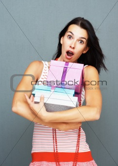Surprised pretty woman holding gifts