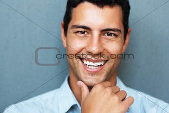 Smiling young man with hand on chin