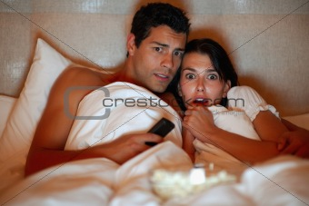 Young couple watching scary movie while lying on the bed