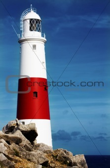 Lighthouse on rocks with blue sky