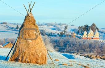 Autumn hoarfrost on mountain village outskirts pasture