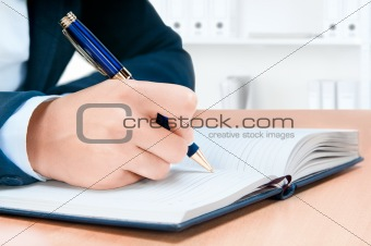 Cropped image of hand of young woman taking notes