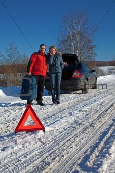Man And Woman Broken Down On Country Road With Hazard Warning Sign
