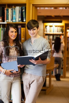 Portrait of students holding blue books
