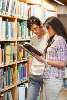 Portrait of young students looking at a book