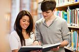 Happy students looking at a book