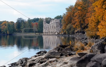 Beautiful autumn nature landscape near river and old castle