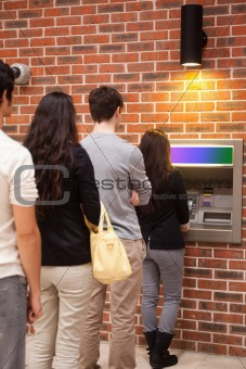 Portrait of people queuing to withdraw cash