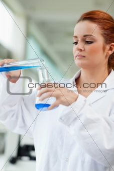 Portrait of a scientist pouring blue liquid in an Erlenmeyer flask