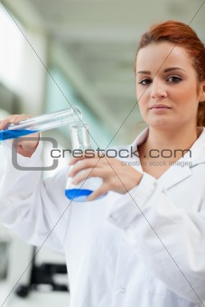 Portrait of a cute scientist pouring blue liquid in an Erlenmeyer flask