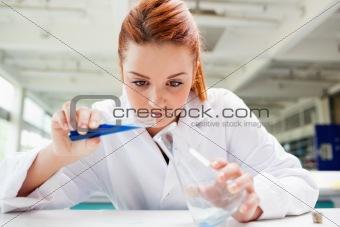 Beautiful scientist pouring liquid