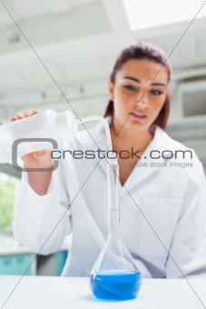 Portrait of a beautiful scientist pouring liquid
