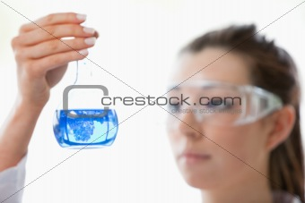 Close up of a scientist looking at flask
