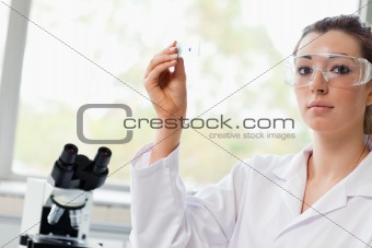 Beautiful science student holding a microscope slide