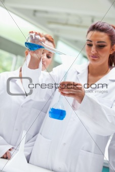 Portrait of smiling scientists pouring liquid into a flask