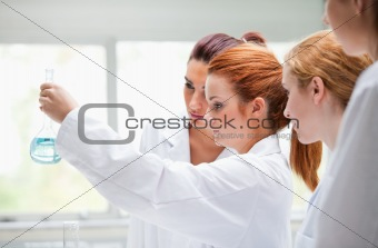 Cute chemistry students holding a flask