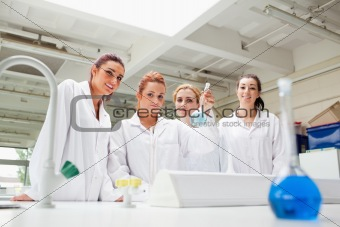 Smiling chemistry students holding a flask