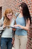 Portrait of a student showing something to her classmate