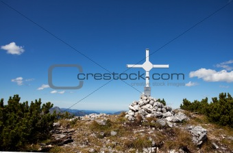 cross at a mountain top in the alps
