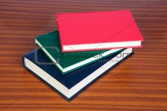 Three hardcover books on a wooden surface