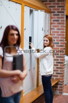 Portrait of a student picking her binder in her locker
