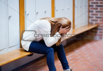 Depressed student sitting on a bench