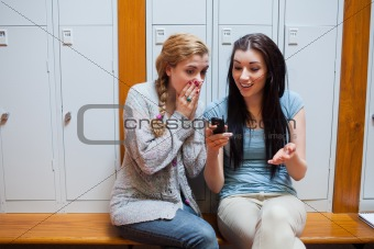 Surprised student showing a text message to her friend