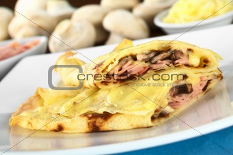 Crepes filled with ham, cheese and mushroom