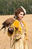The woman in a beautiful old style dress with falcon has a rest