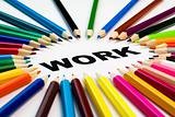 many colored pencils arranged in circle on the word work