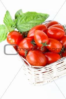 fresh cherry tomatoes and basil over white