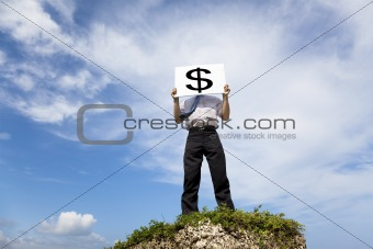 Businessman standing on a peak and holding money mark