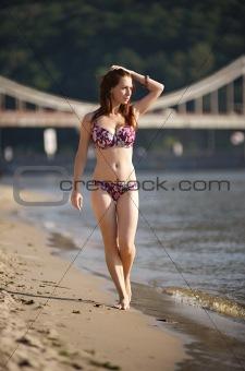 Woman walking through the river beach
