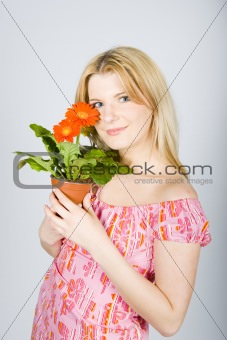 Pretty woman with orange house plant flower