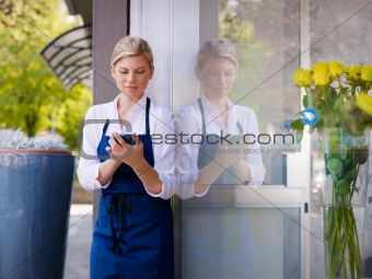 Young woman working as florist in shop and text messaging