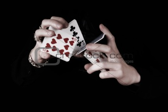Young magicians hands holding a lot of play cards