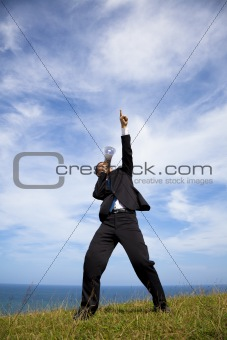 Businessman stand on the hill and holding megaphone with cloud background