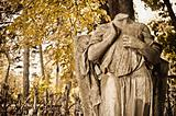 Graveyard scene: headless statue among autumnal trees