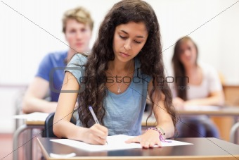 Students taking notes while their classmates are listening