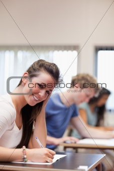Portrait of a smiling woman writing