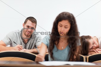 Smiling students writing while their classmate is sleeping