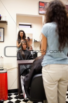 Portrait of a woman combing the hair of a customer