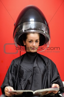 Portrait of a young woman under a hairdressing machine