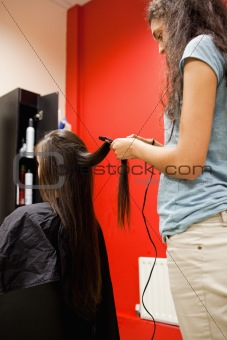 Portrait of a woman straightening hair