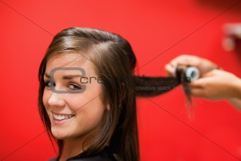 Smiling woman having her hair rolled